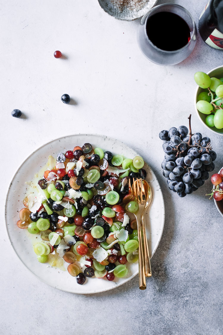 Red, green, and purple grapes with parmesan and olive oil on a white table.