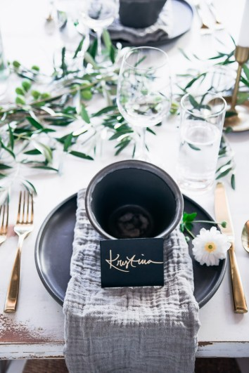 A tabletop place setting styled with dark ceramics, linens, and green foliage.