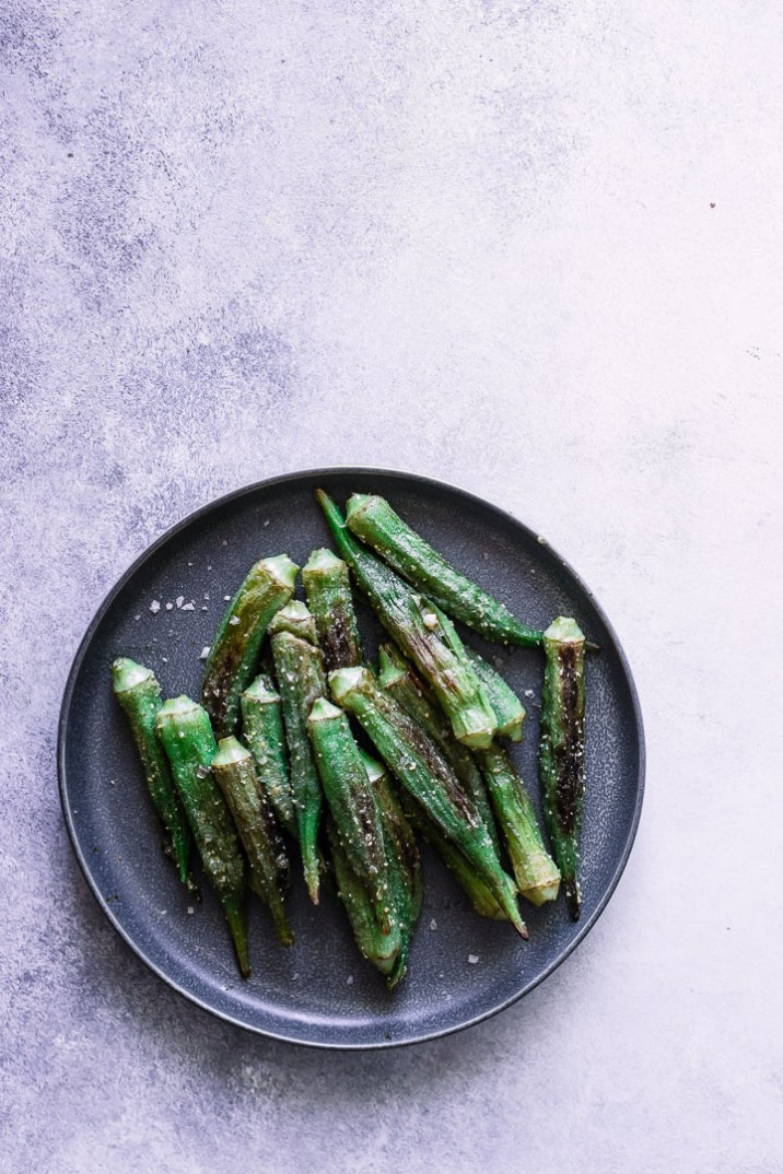 A dark plate with green okra on a white table.