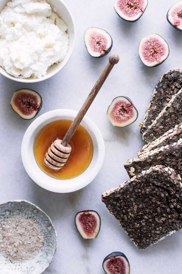 A pot of honey with assorted figs and wheat bread.