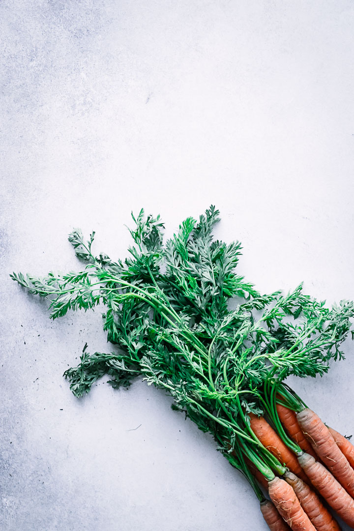 A bunch of carrots with bright green stems on a white table.