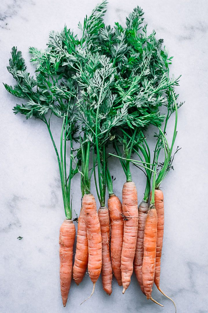 A bunch of carrots with long green stems on a marble table.