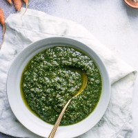 A bowl of pesto made with carrot greens on a white napkin on a blue table.