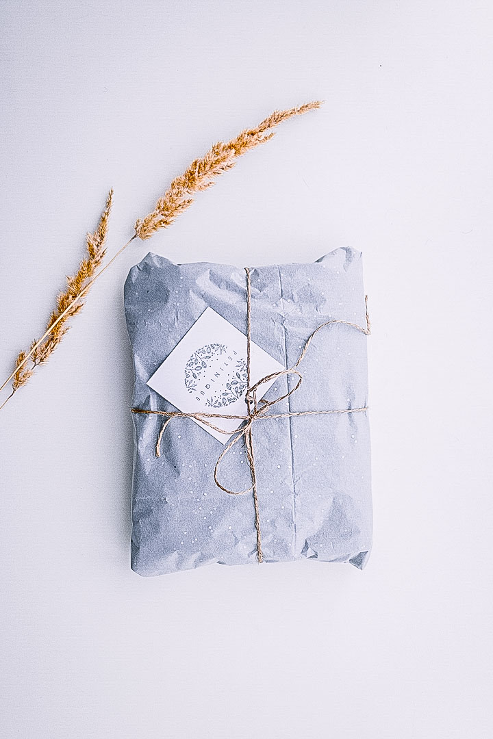A blue gift-wrapped present with a twig of hay