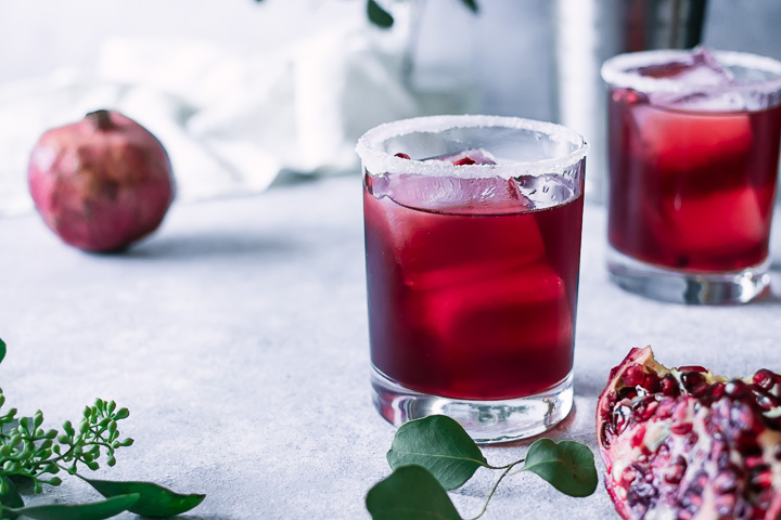 a red cocktail on a white and blue table with a pomegranate