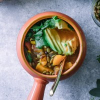 butternut squash chili in an orange soup bowl with a gold spoon