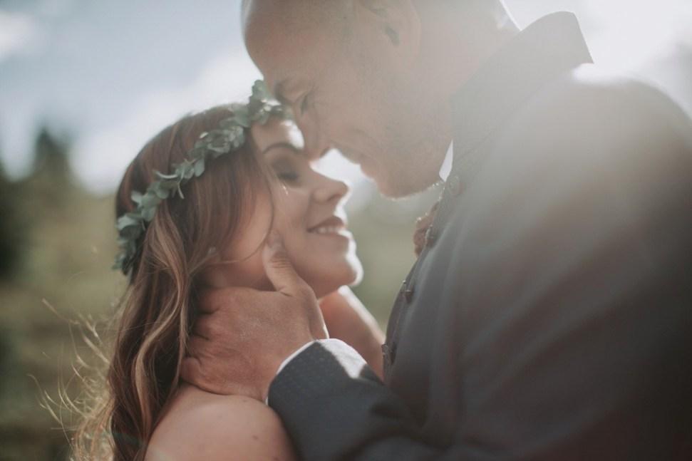 Hochzeiten zu Corona Zeiten, Brautpaar, Blumenkranz, Berge, Sonnenuntergang, Kuss