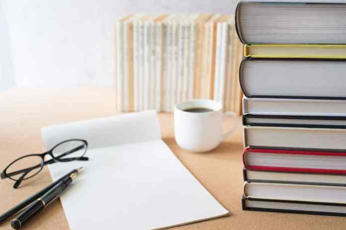 scrivania con libri e fogli bianchi
