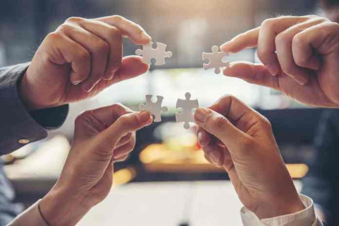 4 mani che uniscono 4 pezzi di puzzle