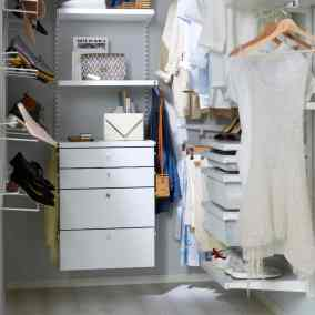 Womens walk in closet with shoe racks, pullout drawers, display trays and shoe racks for high heels and flats