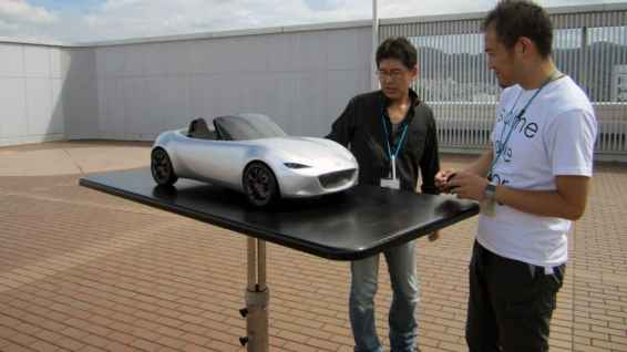 designers look over a model of the ND Mazda MX-5