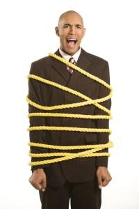 Businessman tied in rope.