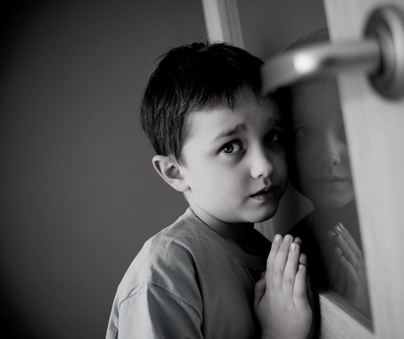 did you grow up in a narcissistic family? photo of child hiding behind door