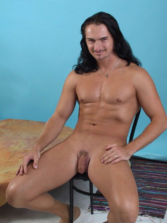 A long haired man sits with a small smile on his lips, his flaccid cock resting between his legs.