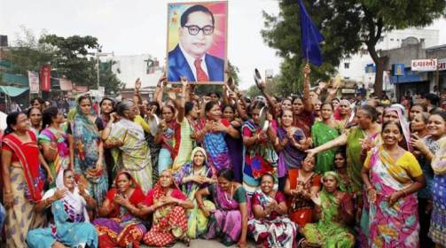 Ahmedabad: Women members of Dalit Community carry a portrait of BR Ambedkar as they block the traffic during a protest in Ahmedabad on Wednesday against the assault on dalit members by cow protectors in Rajkot district, Gujarat. PTI Photo (PTI7_20_2016_000313B) *** Local Caption ***