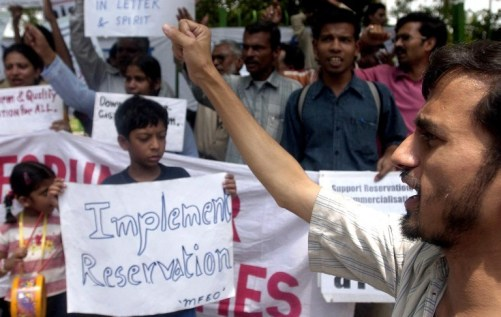 "Pro-reservation activists hold placards and shout slogans as they demand the immediate implementation of the 27 percent quota for backward classes announced by the Indian government in New Delhi, 05 June 2006. Resident doctors in India's capital bowed to a Supreme Court directive and ended a 20-day strike against higher college quotas for disadvantaged students ""in the interest of patient care"". / AFP / MANPREET ROMANA"