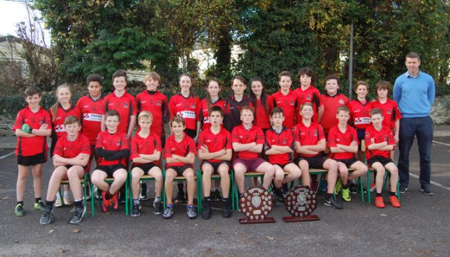 Front left: Sam Buckley, Marc Long, Peadar Kelliher, Finn Kennelly, Sean Dineen, Cian Doyle,(Captain),Patrick Lyons, Harry Kelly, Robert Brooks, Ted O'Gorman. Back Left: Tom Cahillane, Aimee Coffey, Maksym Leon, Darragh O'Brien, Charlie Keating, Abigail Murphy, Alicia Burke, Eddie Moroney, Sophie Dennehy, Darren Ryan, Rocco Sheehan, Matthew O'Connor, Luke Murphy, Ryan O'Leary, Mr. Corcoran, teacher, missing from picture Cian Myers and Mr Kelly, teacher. Fossa School were crowned County Football Division One Champions 2016/2017 for a historic first time on Wednesday November 16th in Austin Stack Park Tralee. They defeated St Olivers Ballycasheen in a thrilling encounter after extra time under floodlights in front of a large crowd. Despite playing against a strong breeze St Olivers dominated the first half. Alex Hennigan the St Olivers centre half forward was proving to be a threat every time he was in possession and his team deserved to be a head at the interval by 5pts to 3pts. Patrick Lyons kicked a point immediately after the resumption to leave the minimum between the teams but after that St Oliver's hit a purple streak by scoring four unanswered points. With three minutes left on the clock St Oliver's led by 9pts to 4pts. Fossa then reduced the margin to 4pts with another Patrick Lyons free. Suddenly the game took a dramatic turn when Fossa's centre half forward Darren Ryan scored a brilliant goal, low and hard into the Oliver's net leaving a point between them as we were entering added time. Fossa won the next kick out and Ryan O Leary scored a wonderful equalising score from out on the wing against the breeze. The tension was palpable in the crowd as both sides tried to manufacture a late winner but the referee soon blew the final whistle to signal extra time. The excitement was at fever pitch as both faced into extra time. Fossa made the brighter start and went ahead by two points scored by Patrick Lyons and Ryan O Leary. St Oliver's showed tremendous fightin