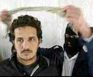 A masked Iraqi National Guardsman blindfolds a detainee suspected of having links with foreign militants, Basra, Photo by Atef Hassan/ Reuters