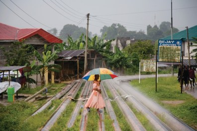 Oil pipelines create a walkway for this young woman through the village of Okrika Town.