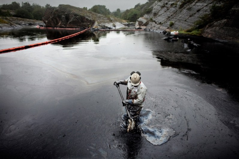 A man cleans some of the worst affected areas around Langesund following an oil spill. First the workers gather the oil, then a truck sucks it up. The 167 metre long cargo ship Full City ran aground at Saastein, just south of the town of Langesund, carrying around 1,000 tons of heavy oil. More than 200 tons was spilt into the sea, polluting some of Norway's most pristine shores, islands, beaches and bare rock-faces. Soon after the accident, the fight to remove the oil started. Volunteers worked with their hands, removing oil from stones, as larger ships worked to gather the huge oil spills floating in the sea.