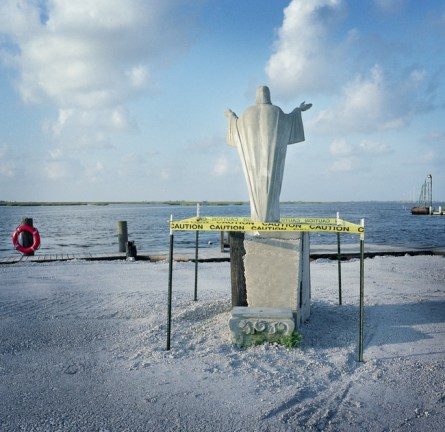 June 2010 A statue of Christ faces the water at the private fishing marina in Pointe Aux Chene which was leased to BP as a staging ground for BP's clean up operations after the oil spill. BP employees surrounded the statue with a temporary barrier while heavy machinery operated on the grounds. The company hired local fisherman who used their own boats to skim oil from the water and deliver and lay boom in an effort to protect shorelines. Commercial fishing remained closed for several months after the spill and oyster grounds continue to be off limits to commercial use. The markets for Gulf seafood have yet to recover. Photo: Kael Alford/Panos Pictures