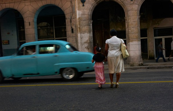 Woman crossing a busy street of downtown Havana. 1950 or 2013? November, 2013.