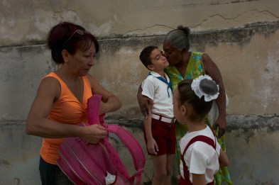 A kiss before school: a mother says good bye to her boy just before entering school. Mothers in Cuba look to care for their children a lot. Regla, November, 2013.