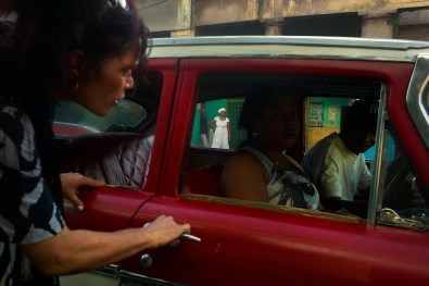 Taxi in Habana. Taxis are shared and normally are inexpensive. The lady is asking to the driver which way he goes. November, 2013.