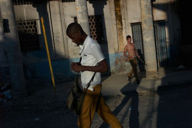 School boy going home after school and a boy playing baseball in the street with a broom stick. Regla, Havana, November, 2013. Regla is a suburb of Havana accessible by ferry just 5 minutes away from Habana Vieja.