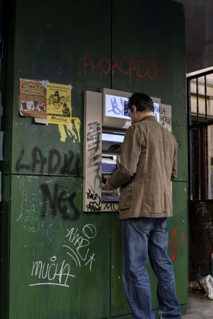 A man uses a Bankia cash machine covered in anti-government and bank graffiti. Bankia is one of many banks in Spain that is currently evicting people from their homes.