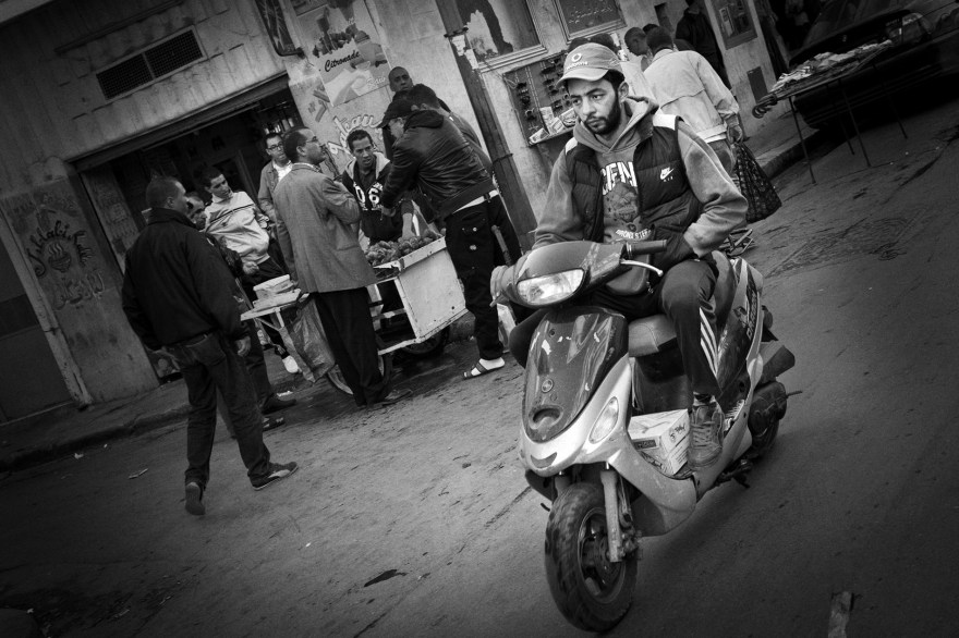 Man rides a scooter through the street in north Tunis