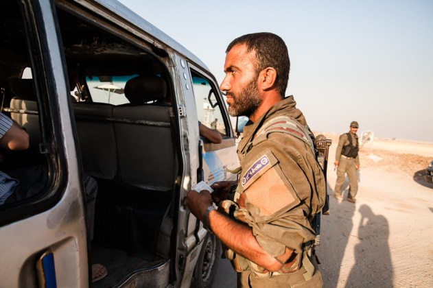 A checkpoint manned by Sutoro Syriac police. Each car is inspected, in fear of car bomb attacks. Near Tirbespiyeh, Syria, June 2014