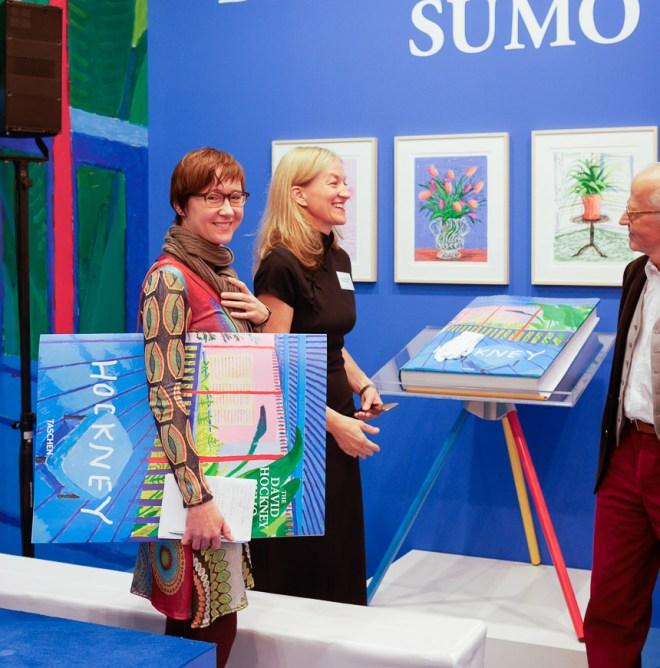 Das Lebensswerk von David Hockney im größten Buch der Buchmesse. Besucherin mit dem größten Buchprospekt der Messe am Stand des Taschen Verlags.