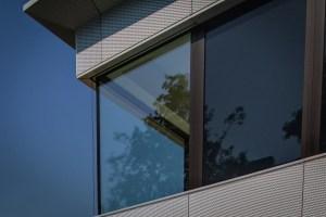 Im Fenster des Gebäudes spiegelt sich ein außen stehender Baum - und er scheint im Inneren des Gebäudes zu sein. Hier lohnte sich ein Ausschnitt aus dem Foto: Natur im Gebäude? Gehört Naturverbundenheit zur Corporate Identity?
