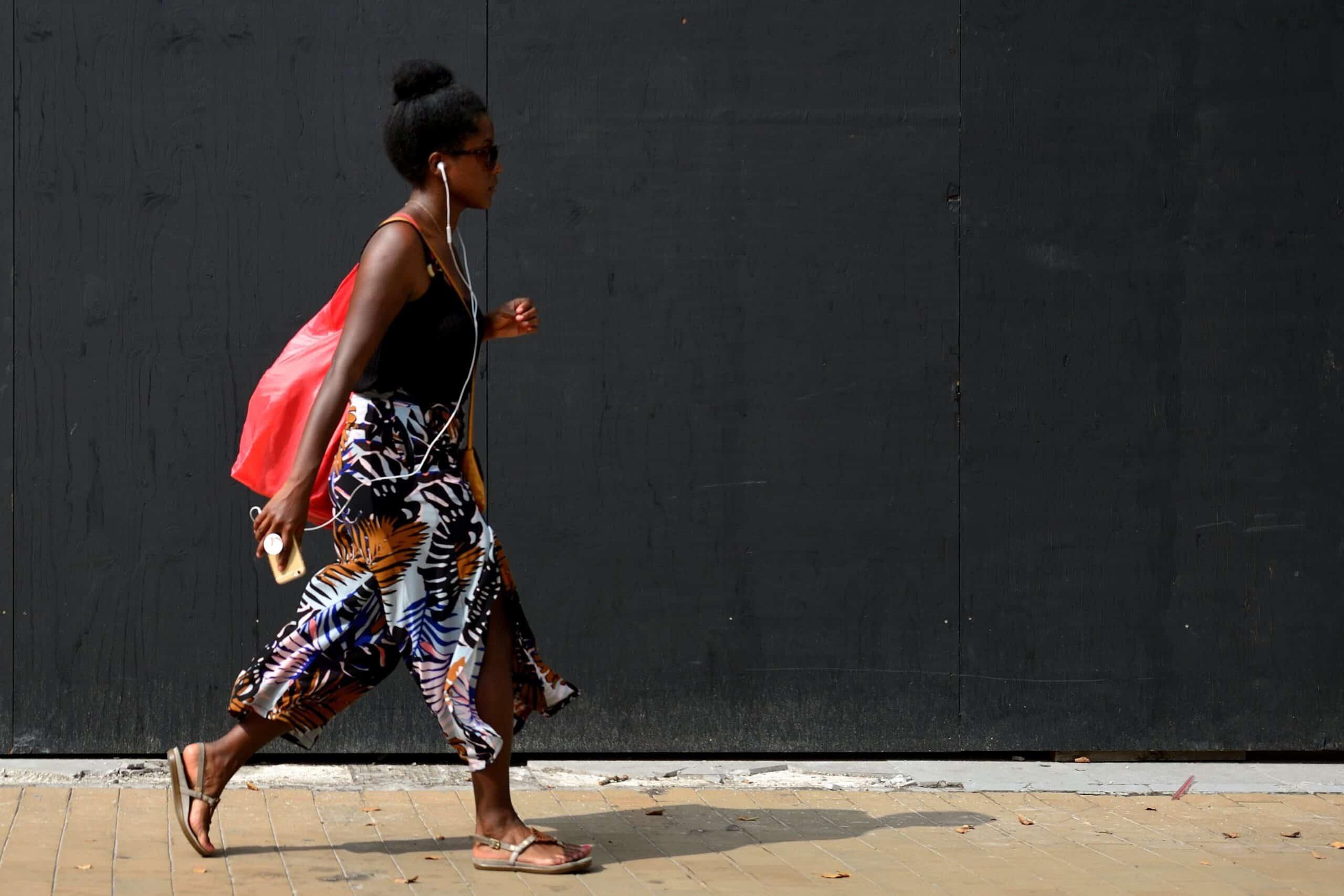 Vrouw loopt voor donkere wand tijdens workshop straatfotografie