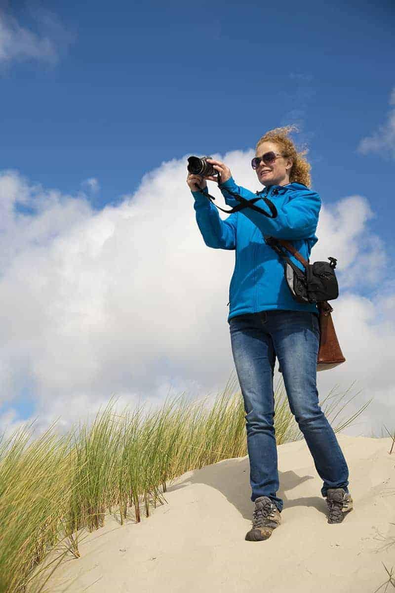 Inez fotografeert vanaf een duin tijdens het Fotoweekend Ameland