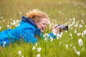 Lachend in het gras aan het fotograferen. Fotoreis Ameland.