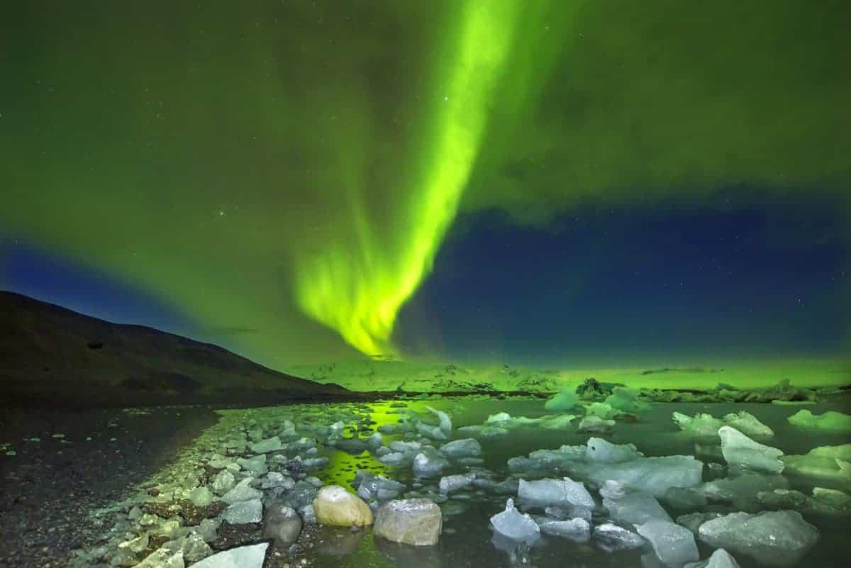 Het schitterende groene Noorderlicht danst boven het ijsschotsenmeer Jökulsárlón op IJsland.