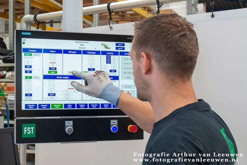 Bedrijfsfotografie, man stelt de software in op de computer voor de productie.