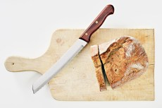 Rustic bread with a knife on a wooden cutting board