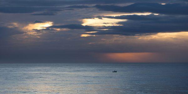 Et majestetisk lys over havet når dagen gryr over Costa del Sol og enslig fiskebåt er ute på jakt etter dagens fangst.