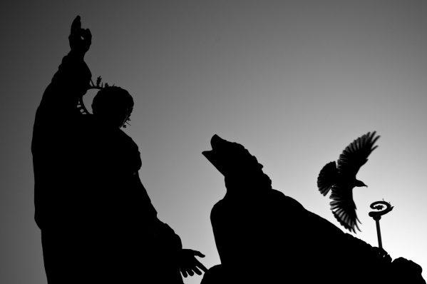 Silhouetter av statuer og fugler ved Karlsbroen i Praha.