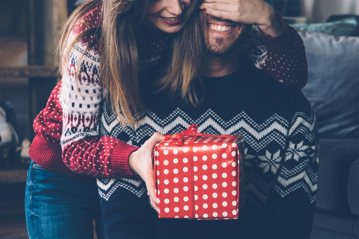 Woman giving Christmas gift to beloved