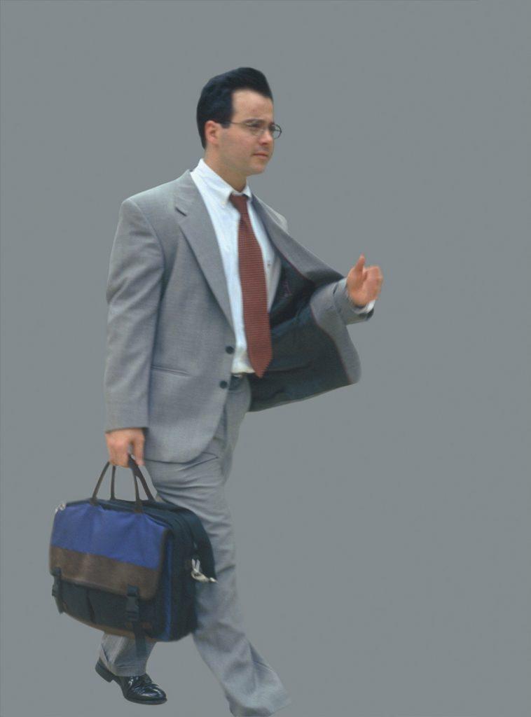 Mann mit grauem Anzug vor grauem Hintergrund mit blauer Tasche