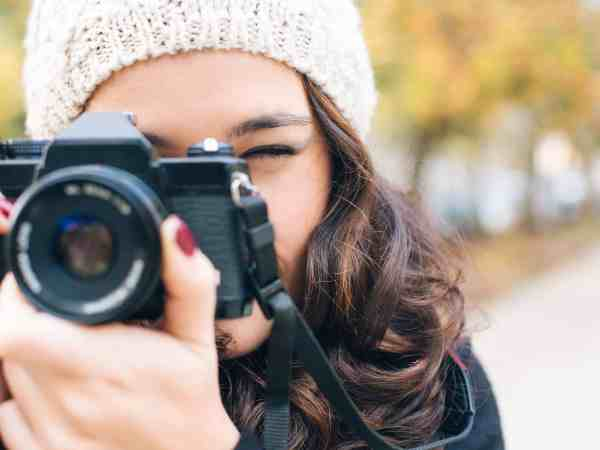 Close up of a young beautiful woman with an analog camera shooting to you in autumn