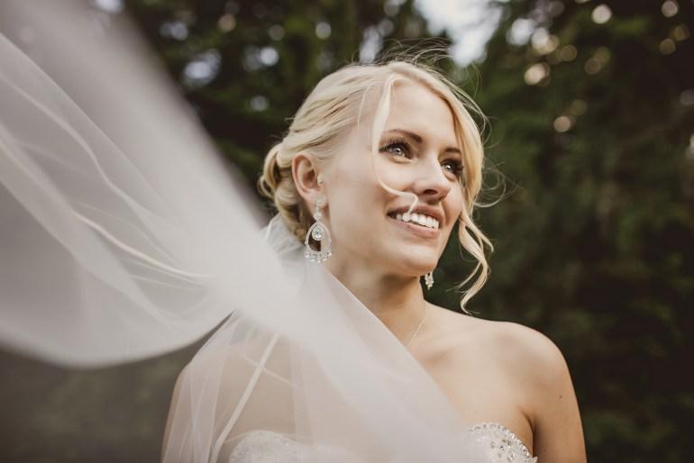 Brautschleiher weht auf den Hochzeitsfotos im Wind.