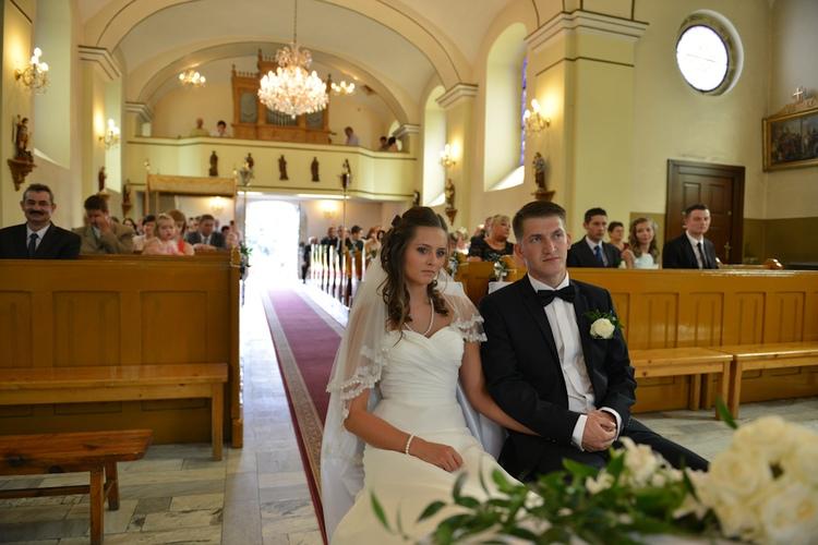 Para młoda w kościele z rodziną w tle