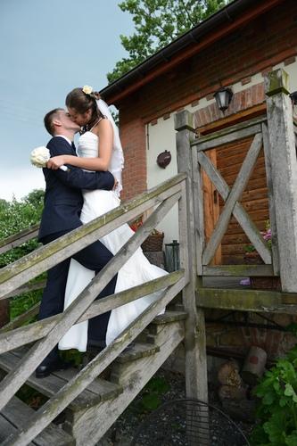 Zakochana para młoda na tle domku, ślubny plener fotograficzny