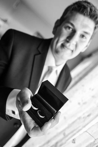Pan młody pokazuje obrączki przed ślubem.