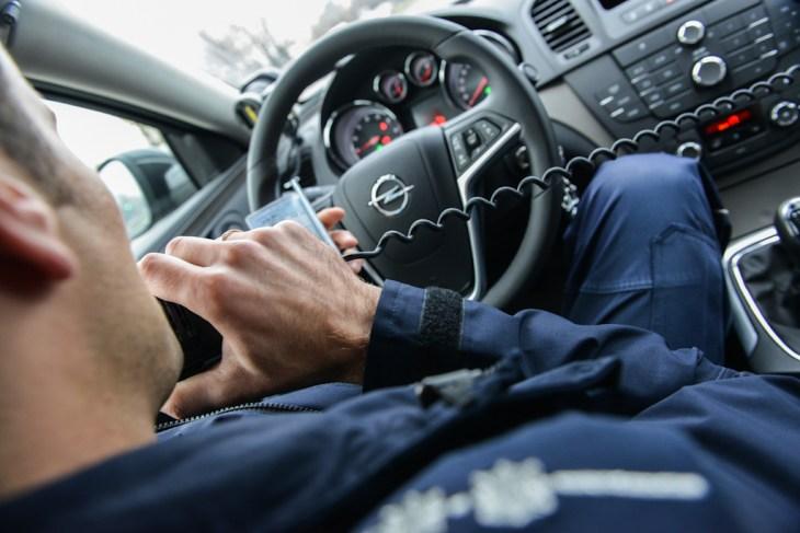 Sprawdzanie kierowcy przezpolicyjne radio wnieoznakowanym radiowozie